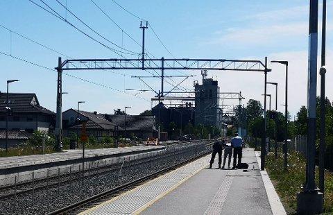 Politiet pågriper her en av de to personene på jernbanestasjonen i Askim fredag formiddag.