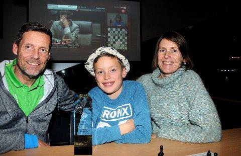 MESTERLIG: Nicolai Østensen sammen med pappa Jan Helge og mamma Ingvild. Skotfoss-gutten brukte                                                      bare to måneder på å bli bedre enn pappa i sjakk. Etter to år var Skotfoss-gutten best av alle under ti år i Norge. Her med pokalen, mens Magnus Carlsen spiller for en ny VM-tittel i bakgrunnen.