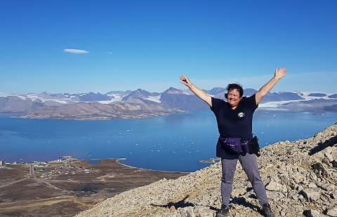 LIVET PÅ SVALBARD: Britt Blom Bredesen bor og jobber i Ny-Ålesund på Svalbard på andre året. Hun elsker det litt annerledes livet. Her jubler hun på toppen av Zeppelin-fjellet med Ny-Ålesund nede til venstre.