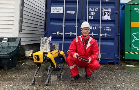 Kevin Kaldvansvik med robothunden Spot på Kværner Stord.  Bak en kontainer påført en QR-kode som roboten bruker til å identifisere hvor utstyr befinner seg til enhver tid.