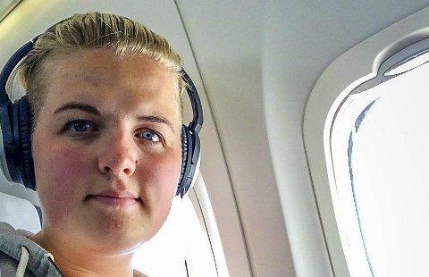 NYTER TID EN BORD: Cecilie Larsen (23) har i tidsrommet 14–26. juli fløyet 49 flystrekninger i hele Norge. Nå har hun opparbeidet seg diamantkort, og kan nyte ekstra komfort når hun snart skal ut å fly igjen. (Foto: Privat)