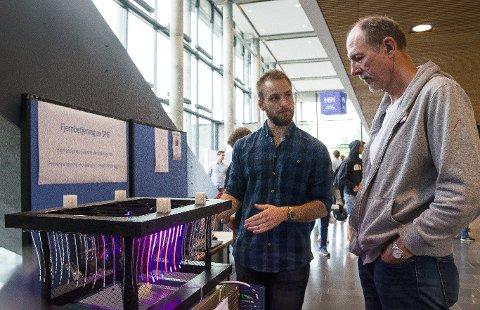 IKKE DISKO: Det er ikke diskolys til fiskene, men et pulserende strømgjerde rundt merdene som holder lakselusa borte, forklarer Martin Davidsen (t.v.) til prjosjektleder Jørn Krogh.