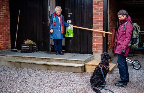 FÅR HJELP: Solveig Viste og hunden Saga har levert handleposen ved ytterdøra til Karina Aas (93). Hun er veldig fornøyd med tilbudet Frivilligsentralen i Ås tilbyr dem som trenger litt ekstra hjelp til handling og hjemtransport av varer.