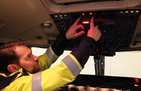 COCKPIT: Testing og kontroll av brannsløkkingssystemet til dei to motorane på flyet er berre ei av mange oppgåver Bjarte Haugnes og resten av flyteknikarane jobbar med på Florø lufhamn kvar einaste natt.