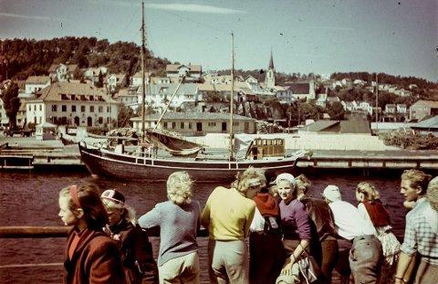 På tur til Kragerø: En båt, trolig kystruta er på vei mot Dampskipsbrygga en sommerdag tidlig på 1960-tallet. En rekke personer står ved skutesida og følger innseilingen. Bak sees Jernbanekaia og tomta til venstre i bildet kan man se den gamle kiosken til Torjussen. Da dette bildet ble tatt vardet ikke vanlig med fargefoto.