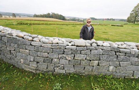 Forseggjort: Kirkeverge Jens Erik Undrum er stolt av den fine steinmuren utenfor den nye kirkegården. De to feltene nærmest ham er til kistegraver. FOTO: STIG PERSSON