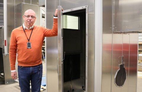 Støydemping: Tor Henning Gulbrandsen ved et av de støydempende kabinettene som produserer ved Slåttland Mekaniske. Rammeskonstruksjonen er den samme, men skreddersys hvert oppdrag etter hva sm skal lydisoleres.