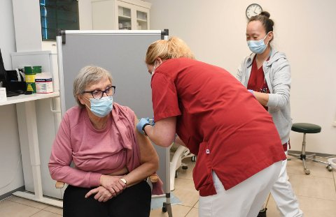 Først ut: Wenche Mikkelsen jobber som helsefagarbeider på Tømmerli. Torsdag fikk hun føste dose med koronavaksine. Jobben ble utført av Anne Grete Børresen og Maria Winther.