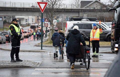 VAKTHOLD: Både trafikkvakter og politi passet på at elevene kom seg trygt over gangfeltet.