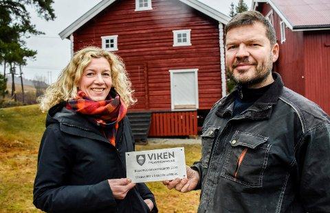 PRISVINNERE: Marte Lerberg Kopstad og Bernt Gran foran stabburet de har brukt 600.000 kroner på å restaurere. Belønningen ble bevaringsprisen fra Viken fylkeskommune.