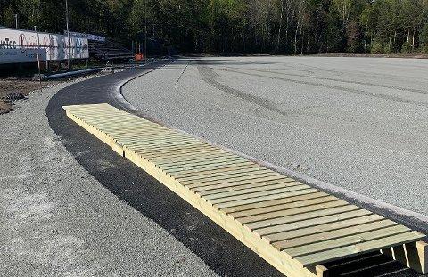 MYE GJORT: Arbeidene med de to kunstgressbanene på Teie nærmer seg stadig slutten. I forgrunnen på dette bildet fra hovedbanen ligger en bro som skal monteres ute i terrenget på den nye sykkelbanen.
