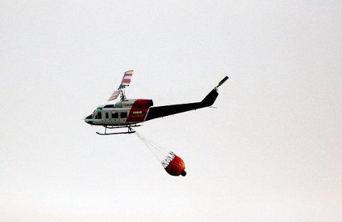 Et brannhelikopter i lufta over Tønnesland gård  tirsdag kveld, etter at skogbrannen i Bjelland i Marnardal var kommet under kontroll.  Brannvesenet frykter imidlertid at flammene blusser opp igjen onsdag morgen.