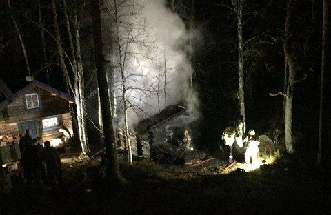 BRANN I BADSTUA: Det begynte å brenne i ei badstu på Åsnes Finnskog lørdag kveld. Badstua ble totalskadet i brannen. Foto: Sverre Viggen