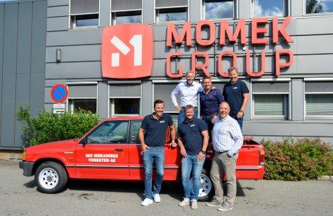 Bak fra venstre: Styreleder Wiggo Dalmo, konsernsjef Roger Skatland og Haakon Andersson, daglig leder i Momek Tech Team.  Foran fra venstre: Roger Halsen, prosjektleder i Momek Tech Team, Freddy Mulstad, daglig leder for Momin og Frank Åsheim, prosjektleder i Momek Tech Team. Og bilen? Det var en gave til Wiggo Dalmo. Det er en kopi av den første bilen som han startet Mo mekaniske verksted med, det som senere ble Momek.