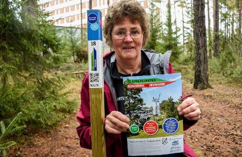 STOLPEJAKT: Marit Tønnessen ved en av de 60 stolpene du kan jakte på. Brosjyren hun viser fram inneholder kartene over de fire områdene med stolper.