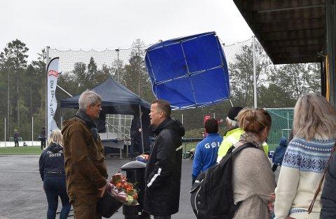 HOLD PÅ TELTET: Bak ordfører Bjørn Ole Gleditsch og GØIFs speaker Anders Mehlum Hasle tok vinden tak i det ene grillteltet. Hadde det ikke vært for ballnettet bak er det usikkert hvor teltet hadde tatt veien. FOTO: Vibeke Bjerkaas