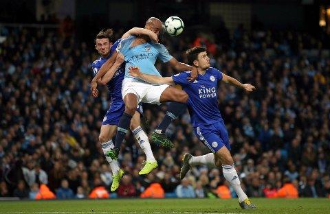 Manchester Citys Vincent Kompany (i midten) og Leicester Citys Ben Chilwell (til venstre) og Harry Maguire kjemper om ballen. Kompany ble matchvinner med sitt drømmetreff i det 70. minutt.
