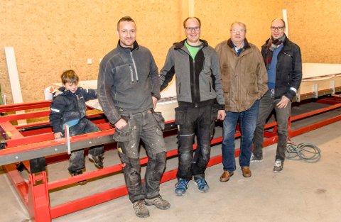 Første kunde Oddbjørn Pettesen sammen med bedriftsledelsen foran jiggen med den første produserte veggseksjonen. Fra venstre Aldin (4) Wold, Tarald Wold, Henning Kristiansen, Oddbjørn Pettersen, og Stian Kristiansen