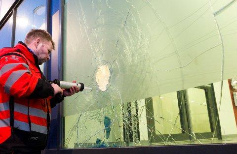 Hele seks vinduer var slått inn og knust, i NAV-bygget. Glenn Helminsen  fra SOS-redning, sikrer så ikke skadene skal bli enda verre.