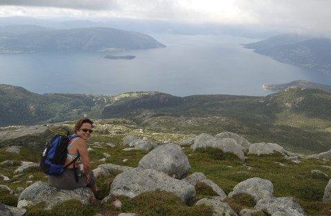 PÅ TOPPEN: Solveig H. Hauge nyter utsikten over Hardangerfjorden fra 800 meters høyde. Ænes ved fjorden til venstre. Varaldsøy i bakgrunnen. Foto: Kristin Helgeland Hauge/HAUGESUND TURISTFORENING
