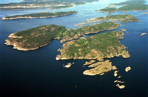 ØYANE sett i luftig perspektiv fra sør med Arøya til venstre og Stokkøya til høyre. Mellom de to øyene går Stokksundet. Den vestre av holmene sør for Stokkøya er den geologisk berømte Låven. I bakgrunnen til venstre ser vi Geiterøya og Langesund.