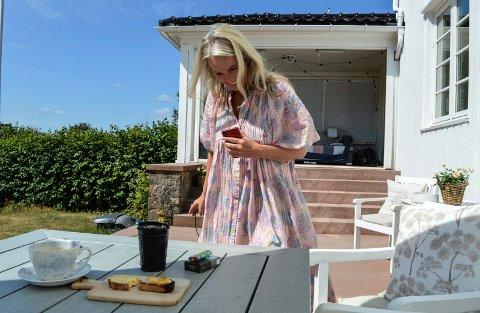 I HJEMBYEN: Nå om dagen bedrives det slaraffenliv med familien på terrassen. Enda mer tid tilbringes på sjø'n. Men Anita Krohn Traaseth har aldri mobiltelefonen langt unna.