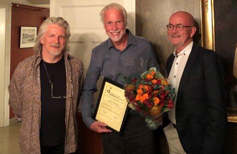 STORT SMIL SOM PRISVINNER: Rolf S. Grundesen smiler bredt med prisen i en hånd, og roser i den andre.