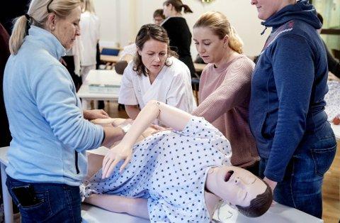 Under kursingen benyttes dukker, jukseblod og løse armer for å gjøre øvelsene mest mulig realistiske. I midten instruktør og spesialsykepleier Aina Kolle.