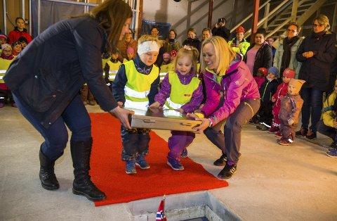 TUNGT: Barnehageleder Vibeke Hillestrøm (t.v.) og styrer Marianne Moe Martinsen hjelper Emil Madsen og Gabriele Mikalajunaite med å legge ned grunnsteinen til nye Skredsvikmoen barnehage.