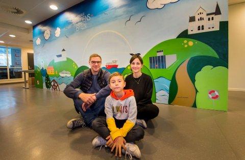 Kunstnerne: Kim Daniel Vedal, Katinka Jørgensen og Rafael Vedal (foran) har laget veggkunsten i lokalene til etat for bygg og eiendom. Kommunens slagord «Den lille verdensbyen» er selvfølgelig med.
