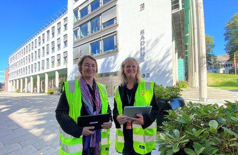 Eiendomsskattesjef Tone C. Aas (til venstre) og  overingeniør Elisabeth Bergstrøm ved geomatikkavdelingen i Fredrikstad kommune iført vestene som takstmennene bruker. Nå får kommunen mer tid på seg til å gjennomføre takseringen og fastsette nye beløp for hver enkelt eiendom.