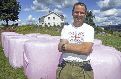 Rosa er kult: Øystein Stensæter på Korshagan på Granavollen lager med glede rosa rundballer til støtte for brystkreftforskning. – De er jo fine, disse rosa rundballene, synes gårdbrukeren.