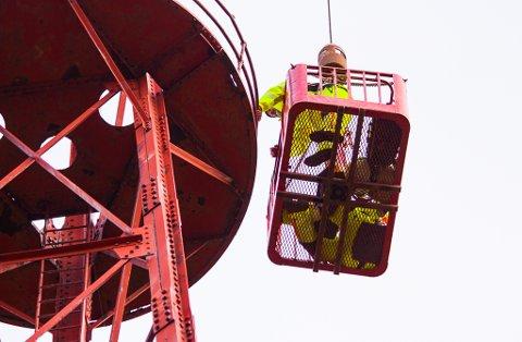 HENGER HØYT: Arbeiderene henger høyt for å kunne sjekke mastas tilstand fra topp til bunn.