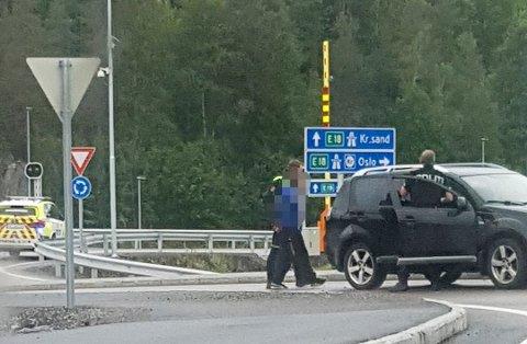 TRUET MED Å SKYTE: Her blir de to ranerne arrestert ved E18 søndag 7. juni.