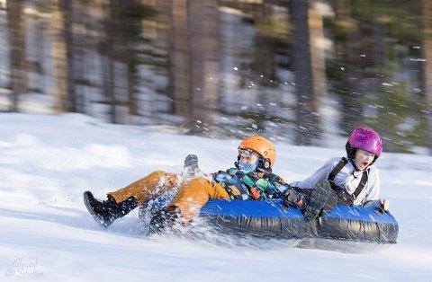 FULL FART: Emelie Mellemstuen (bakerst) hadde det moro   i dobbel tube  i skibakken.