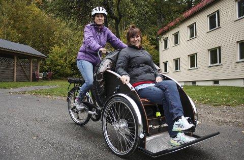 Mule sykehjem har anskaffa seg en elektrisk sykkel med vogn, som de eldre kjøres rundt i. Her ser vi aktivitør på dagavdelingen, Åse Elseth, som sykkelpilot, mens renholdsleder Marit Aaltvedt er fornøyd passasjer.