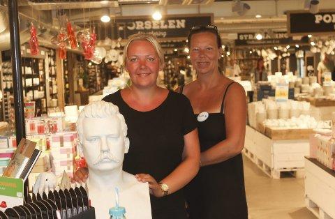 Hektisk hverdag: Helena Teigen og Hanne Myrland håndterer mange kunder denne sommeren. Her poserer de sammen med statuen av grunnlegger, Johan Jeremiassen.