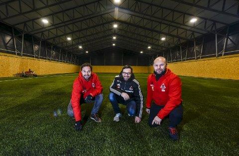 – SE, VI HAR FÅTT GRESS! Åga IL er klar til å slippe fotballspillerne til i nyhallen på Hauknes. Leder i Åga IL, Eirik Bjørkmo (fra høyre), Kjetil Knudsen og Morten Grimsø er meget fornøyd med produktet. Foto: Øyvind Bratt