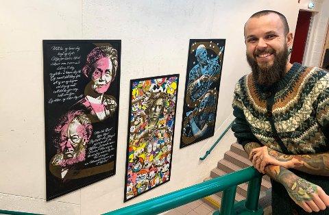 UTSMYKNING: Dino Tomic med maleriene som endelig har kommet opp i foajeen på Notodden videregående skole. Nå blir det trolig mer samarbeid.