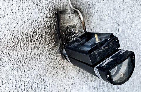 SPRENGT: Denne utelampa ble sprengt ut fra veggen da lynet slo ned i et hus i Rugdeveien lørdag. Elektriker Marius Stokker sier det er enorme krefter på gang når naturens krefter treffer.