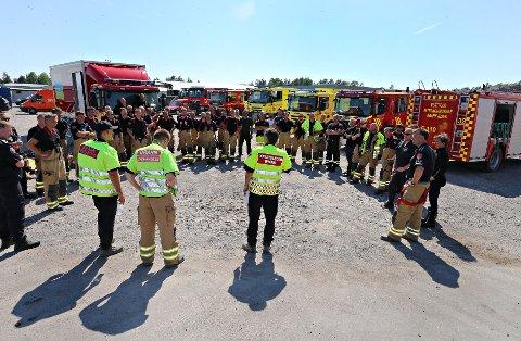 STORE STYRKER: Brannmannskapene måtte innimellom samles for å koordinere innsatsen. Brannsjef Per Olav Pettersen i VIB (med ryggen til) ledet innsatsen på stedet.