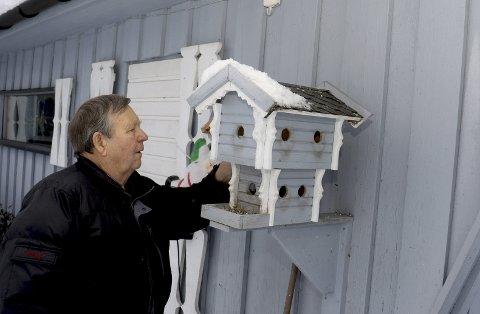 SJEKKER OM DET ER MAT NOK: Kåre Hagen sjekker fuglehuset utenfor eget hus.