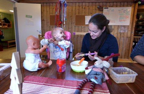 Lov å leke: Ved matbordet sørger hjelpepleier Kristine Lie Stor-Re og de andre ansatte i barnehagen for at Ida Sofie Barra (snart 2) kan leke at hun deler maten sin med dukkene, bamsene og andre, slik at hun selv også skal få lyst til å smake på maten – samtidig som de sørger for at hun får den næringen hun trenger gjennom sonden i magen.