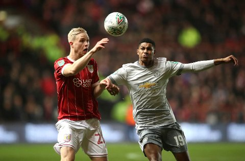 Bristol City's Hordur Bjorgvin Magnusson, left, and Manchester United's Marcus Rashford battle for the ball during the English League Cup Quarter Final soccer match between Bristol City and Manchester United at Ashton Gate, Bristol, England, Wednesday, Dec. 20, 2017. (Nick Potts/PA via AP)