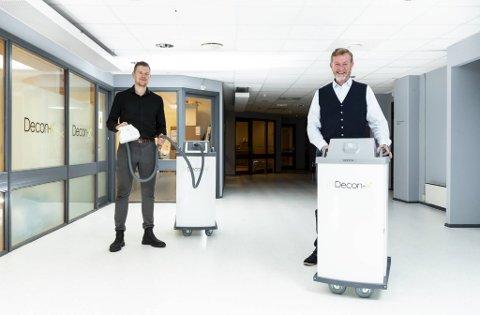 Denne roboten kan desinifisere et helt rom. Gründerne Bjørn Platou (f.h) og Lars Fredrik Tvinde fikk det mildt sagt travelt da koronaen traff Norge i mars.