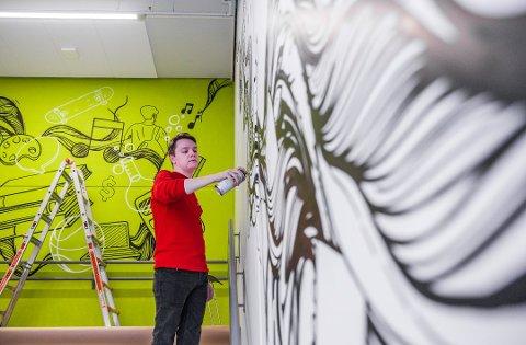 Christoffer Henriksen jobber som grafittikunstner. Her dekorerer han veggen på en ungdomsskole