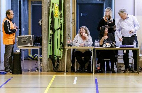 FULL FORVIRRING: Både speaker Øyvind Strøm, Wenche Solberg og Eva Henriksen i sekreteriatet, og NHFs delegat, Helge Johnny Dehlin, fikk hendene fulle da klokka i Remmenhallen nok en gang tok kvelden.