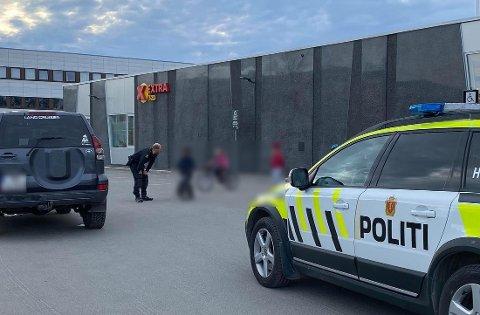 PENGEFUNN: En politibetjent snakker med et barn på stedet. En større pengesum ble funnet i en pose utenfor Extra Elverhøy søndag kveld.