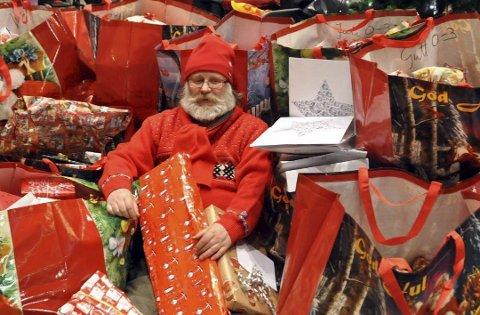 PAKKER: Gisle Christoffersen i Vestvågøy Røde Kors kom nesten bort i pakkehaugen under en tidligere julegaveaksjon.