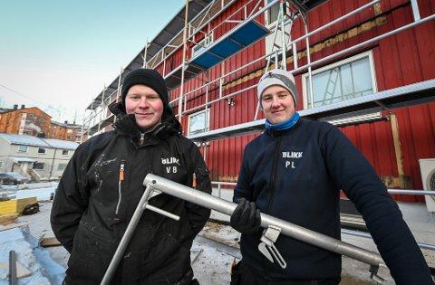 Viktor Brattland (21) og Petter Leistad (21) gjør sitt beste for å holde på varmen når de arbeider ute i kulda.